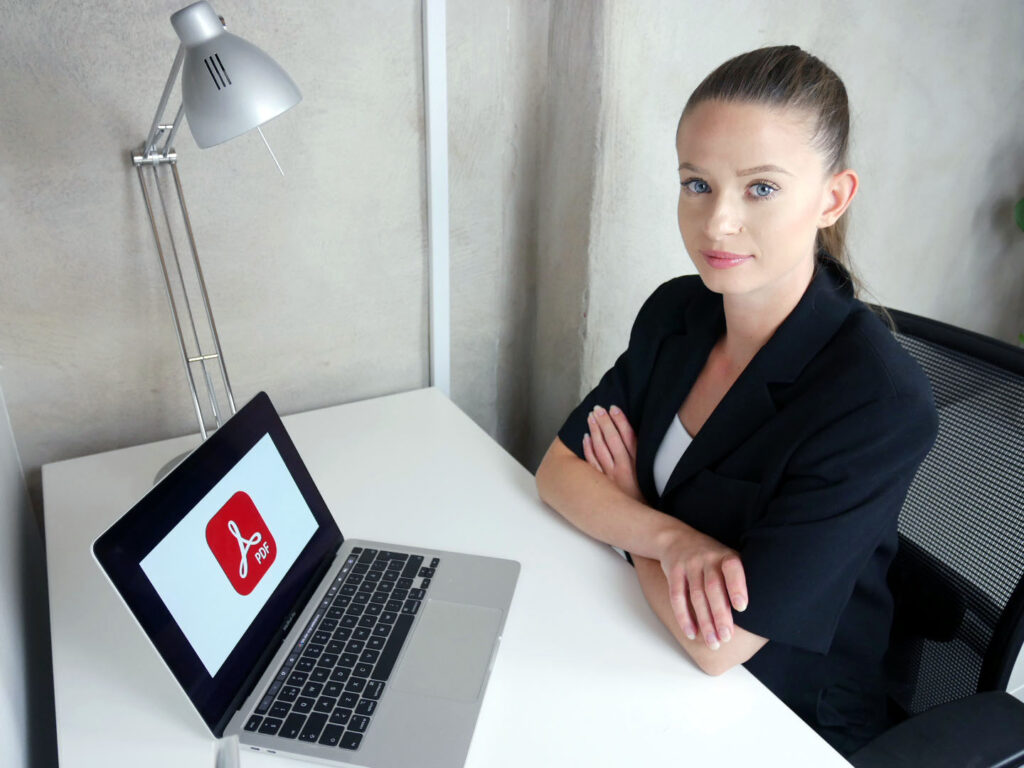 Erica på WCAG Networks kontor framför datorn med bild på PDF.