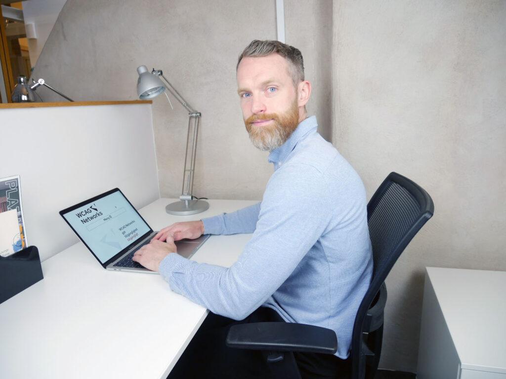 Peter på WCAG Networks kontor framför datorn.